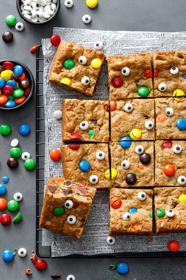 Overhead, squares of Monster Cookie Bars on a dark gray background, small bowl of M&Ms and candy eyeballs