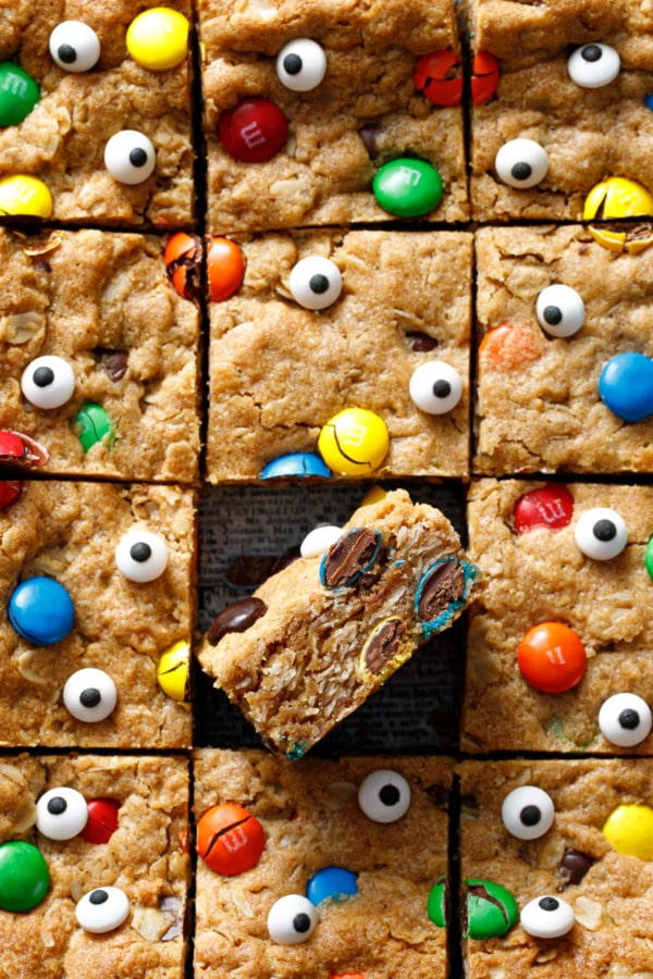 Square grid of cut Monster Cookie Bars, one tilted on its side to show cross-section