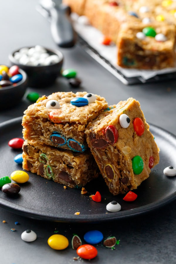 Stack of three Monster Cookie Bars on a black plate, topped with M&Ms and candy eyeballs for halloween