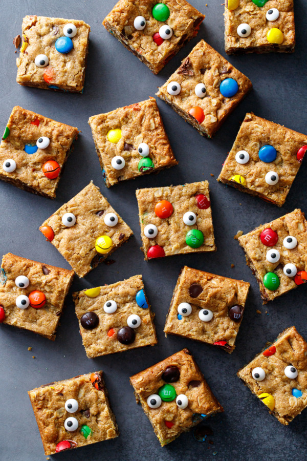Random arrangement of Monster Cookie Bar squares on black background, with candy eyeballs making faces