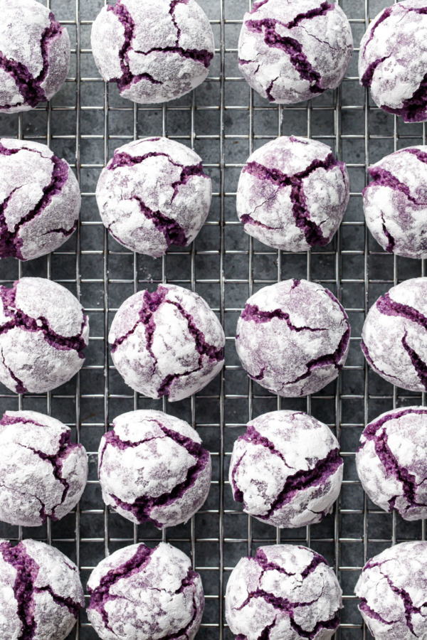 Overhead, wire rack with even rows of ube ameretti cookies, with purple cracks showing through a powdered sugar coating