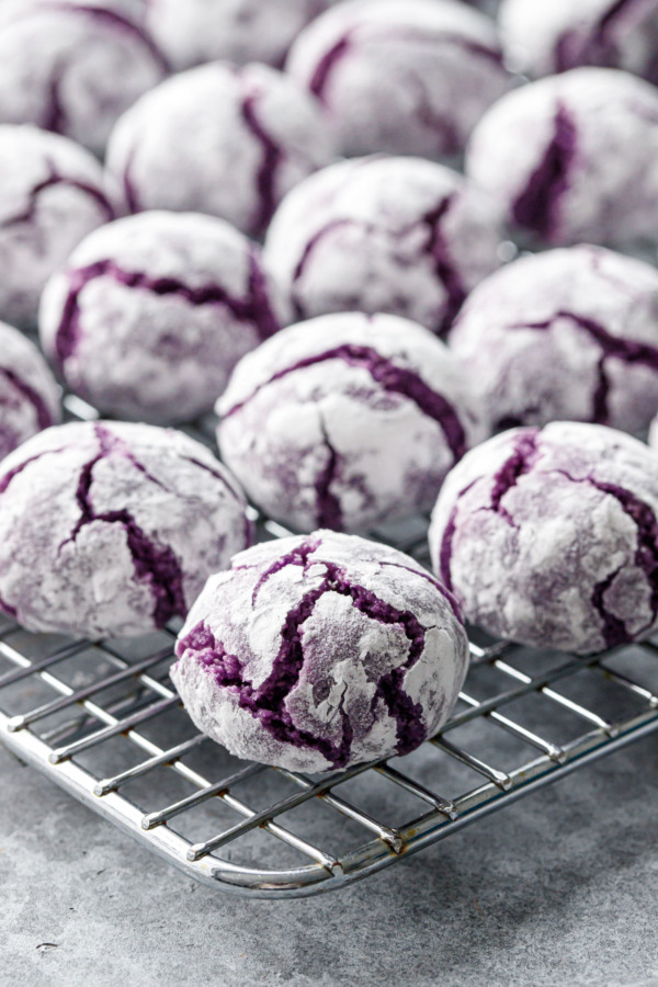 Closeup of ube amaretti cookie on a wire rack, showing the purple crinkle texture and powdered sugar coating.