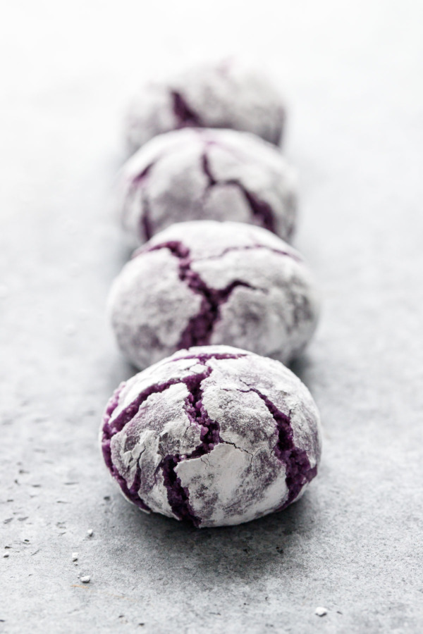Closeup with narrow depth of focus, row of ube amaretti crinkle cookies on a gray background.